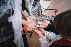 An adult disinfects children's hands before giving them candy on Halloween during covid-19 pandemic