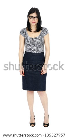 An adult (early 30's) black haired caucasian woman, wearing a dotted shirt and a dark jeans skirt, glancing to her left with a childlike frowny expression and posture. Isolated on white background.