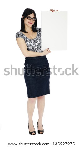An adult (early 30's) black haired Caucasian woman, wearing a dotted shirt and a dark jeans skirt  looking at the camera with a large toothy smile, holding a blank sign. Isolated on white background.