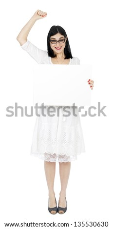 An adult (early 30's) woman holding a blank sign with her right hand, and her left hand raised in a success/winning gesture, while giving the camera a large toothy smile. Isolated on white background.