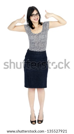 An adult (early 30's) woman, wearing a dotted shirt and a dark jeans skirt looking at the camera with a toothy smile and arms raised in thumbs up motion. Isolated on white background.