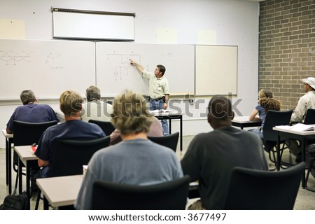 stock photo : An adult education teacher pointing to an electrical circuit ...