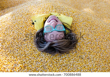 An adult female has her entire body covered and buried in corn kernels in a corn pit, with only her head showing - Shutterstock ID 700886488