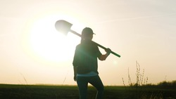An adult girl farmer walks with a shovel on her shoulder across the field at sunset in the sky, a business lady agronomist at dawn works in the field, a man goes to drip the ground and plant seedlings