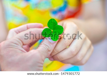 An adult gives the child a four leaf clover. Arms. The symbol of good luck. Good luck wish concept #1479301772