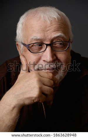 An adult gray-haired man of age with a sly woman looks to the side, resting his head on his hand. Portrait, studio, close-up, focus on the face. Stock fotó ©