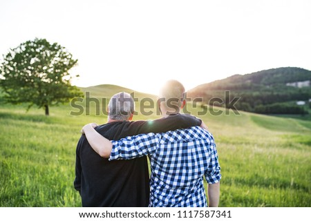 An adult hipster son with senior father standing in nature at sunset. Rear view. Stock photo ©