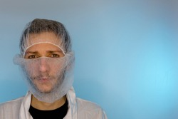An adult male dressed in a white lab coat with a hair net and beard net on. Ready to work in a clean room or laboratory