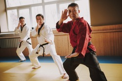 An adult male karate fighter stands in a rack and teaches his students. People repeat after the teacher who shows the karate stand.