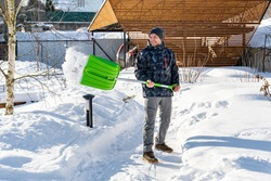 An adult man cleans the paths in the garden from snow in a good mood. Shoveling snow from paths with a shovel on a sunny day. Garden care in winter. Snow falls off the shovel when cleaning snow.