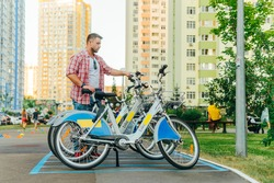 An adult man in a shirt rents a bicycle for a walk on the weekend. City bike rental via smartphone, man puts the bike in place after riding. City online bicycle rental.