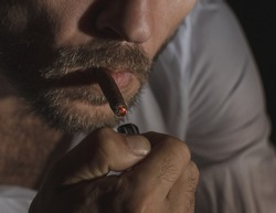 An adult man lights a cigarette butt, close-up photography of the human face, and cigar smoking process. Art photography of smoking man with low lighting and focus on the process of lighting a cigar.