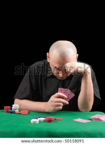 an adult man playing poker . Isolated over black