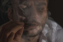 An adult man smokes a small cigar. Face covered with cigarette smoke. Man looking at the cigarette butt through the smoke.