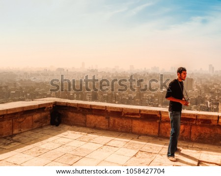An adult middle eastern male photographer standing on the yard outside Mohamed Ali mosque in the Cairo citadel and in the background Cairo cityscapes Cairo, Egypt  #1058427704
