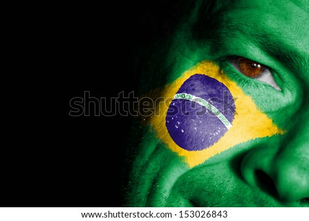 An adult sports fan with his face painted in the colors of Brazil's flag