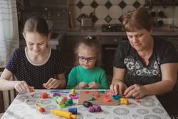 An adult woman and two little girls make plasticine figurines at home. Grandmother and granddaughters are sitting at home. Family Values Concept