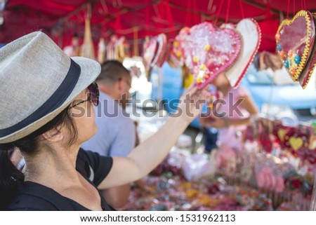 An adult woman buys a biscuit at a market
