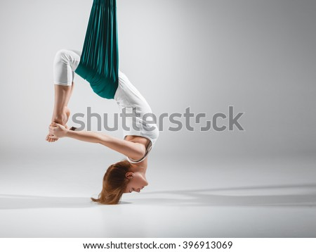 An adult woman practices different inversion - anti-gravity yoga positions in a bright well lit studio.