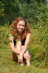 an adult young beautiful European girl is relaxing on nature outdoor sitting on the grass on the background of a forest. vertical photo
