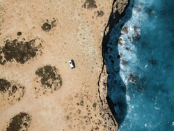 An aerial drone image of a single white van on top of steep cliffside overlooking the deep blue ocean on the Nullabor Plain, South Australia