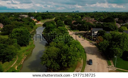 An aerial drone photo of a sunny summer day in Plano Texas next to a river park with a car driving on the street Foto stock ©