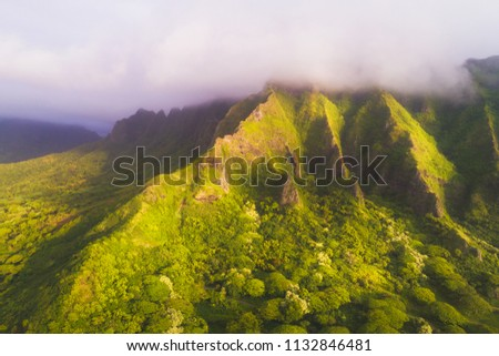 An aerial image of a beautiful mountain ridge with clouds covering the peak. Shot during sunrise. #1132846481