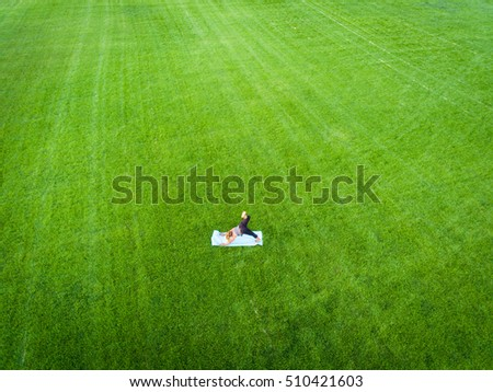 An aerial image of a woman doing yoga in a field of grass. #510421603
