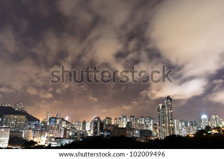 an aerial overlook of hong kong city at night with amazing clouds moving in the sky - stock photo
