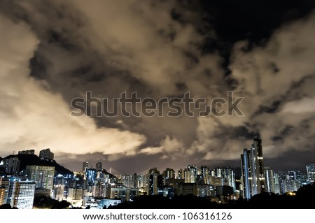 an aerial overlook of hong kong city skyline at night with amazing clouds moving in the sky