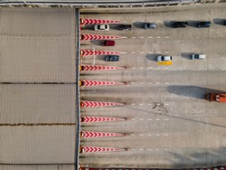 An aerial photo top down of road and highway early in the morning with many vehicles passing thru the toll booths in petaling jaya.