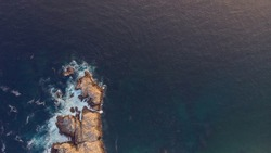 An aerial shot of blue seawater with rocks on a seashore
