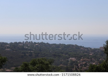 An aerial shot of trees and building near the sea with a clear sky in the background #1571508826