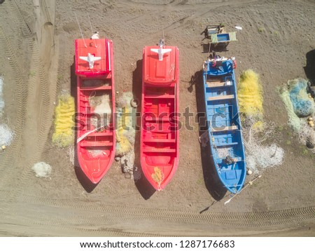 An aerial view directly above of the fishing boats over the sand while a crane try to pull from the sand to the sea the cute fishing boats. Amazing fishery at Chile with all the boats in a row line