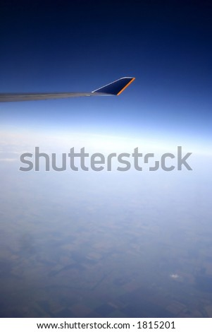 An aerial view from out of an airplane window at high altitude showing ground below - stock photo