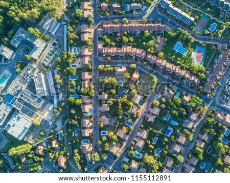 An aerial view from the drone of a neighborhood with its swimming pools inside a forest in the outskirts of Madrid city seeing the urban planning of the area with its home and streets aligned