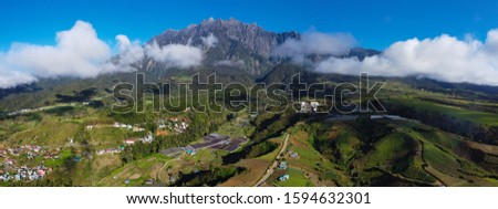 An aerial view Kundasang village,Ranau,Malaysia with Mount Kinabalu background. these images were taken using the combined technique of multiple pieces of panoramas or panoramas