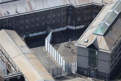 An aerial view of a HMP prison taken from a helicopter in the United Kingdom. The old grey Her Majesties Prison has fences and barbed wire preventing the escape of the jails inmates
