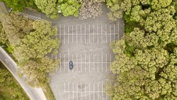 An Aerial View Of A Lonely Car In a Park's Parking Lot in The Evening, Just Before a Cloudy Sunset