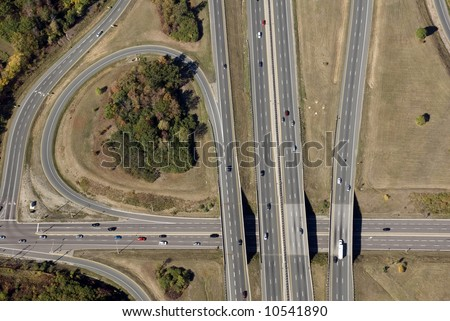 An aerial view of a North American freeway interchange in late summer. (Some of the faster moving cars have very slight motion blur.) - stock photo