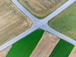 An aerial view of a road intersection surrounded by fields.