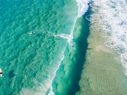 An aerial view of a surfer riding a wave at the beach on the Gold Coast in Queensland Australia