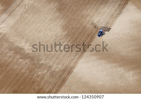 An aerial view of a tractor plowing a field