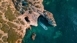 An aerial view of a turquoise shiny sea with a single boat sailing along the coastal cliff in Algarve, Portugal