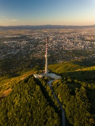 An aerial view of a TV tower on the green hill and dense buildings under a blue sky in Sofia, Bulgaria