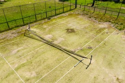 An aerial view of an old unused tennis court in disrepair in a public park in a small regional township