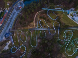 An aerial view of curvy bobsleigh tracks in a beautiful forest