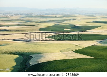 An aerial view of farmland and pivot sprinklers watering the fields.