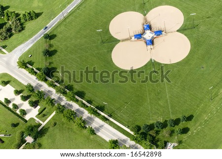An aerial view of four baseball diamonds in a green lot.