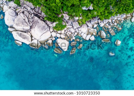 An aerial view of Koh Tao island showing beautiful landscape of green forest and blue water in Thailand.